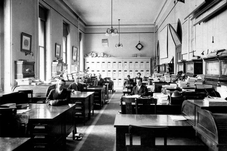 Journalists working at their desks in the early 20th century