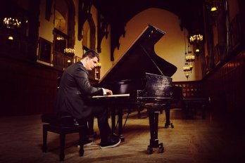 Colin Dutcher playing piano with room with high-vaulted ceilings