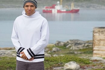 Natan Obed poses on front of harbour with ship in background