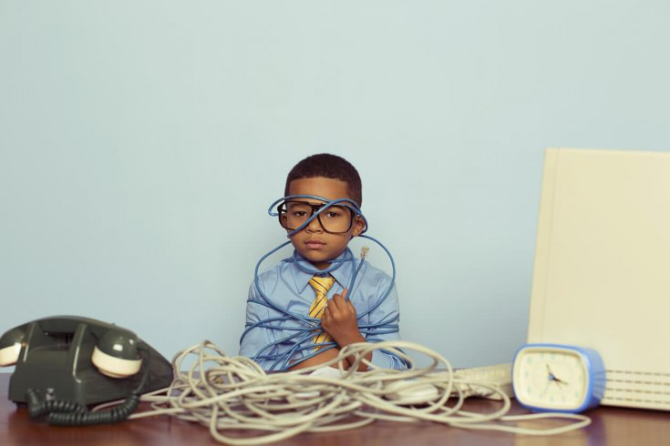 Kid wearing suit and glasses enrobed with computer cords