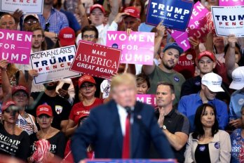 Crowd displays political campaign signs behind president donald trump