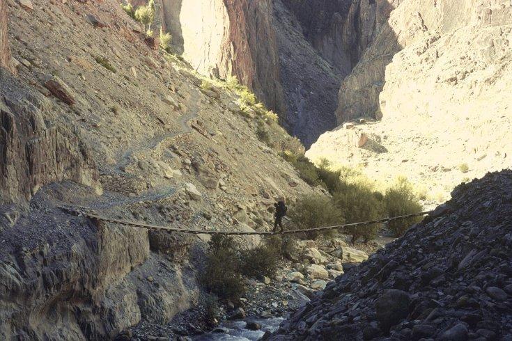 Man walking over wooden bridge in rocky valley
