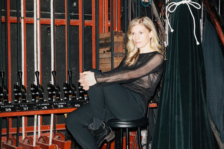 Woman sitting on stool backstage
