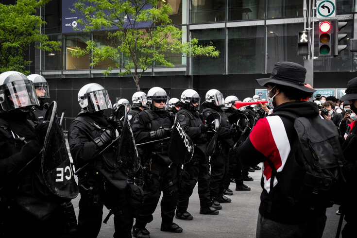 A photo of a protest, with police forming a line opposite the protestors.