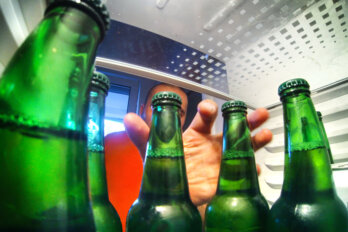 A photograph taken from the interior of a fridge, from behind a row of green beer bottles. The door is open and a man's hand is reaching towards the bottles.