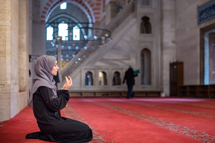 A Muslim woman in a headscarf and hijab kneels in a mosque. Her hands are held up in front of her body prayer.