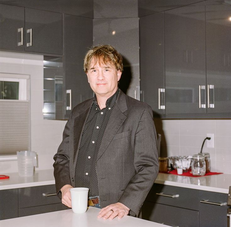 Alexander stands at a countertop in a sleek kitchen and holds a cup of coffee. He is wearing a grey blazer and a black shirt with white polka dots.