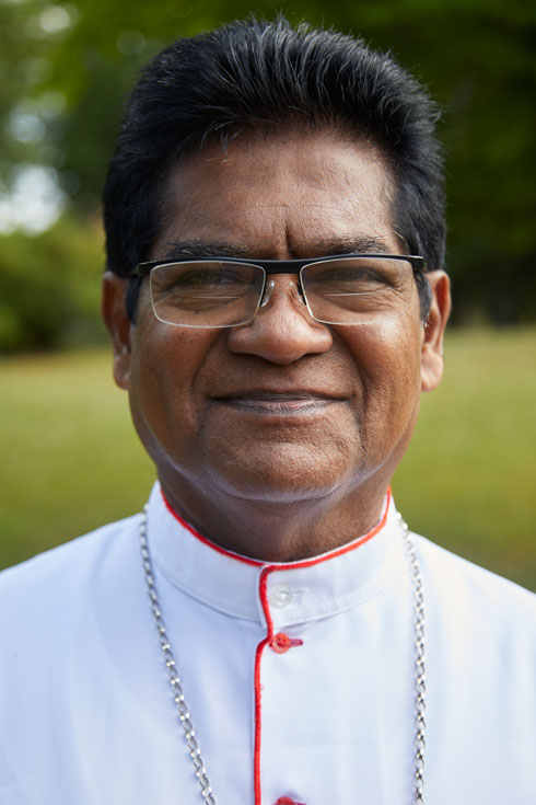 A closeup photo of Sampathawaduge Maxwell Grenville Silva, Auxiliary Bishop of Colombo, who is smiling into the camera.