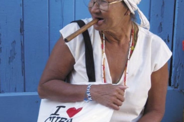 """A woman in Havana carries one of Alejandro Diaz's """"I ♥ Cuba"""" vinyl beach bags. The bags, which play with ideas about tourism and merchandising, were handed out at the Havana Biennial last fall."""