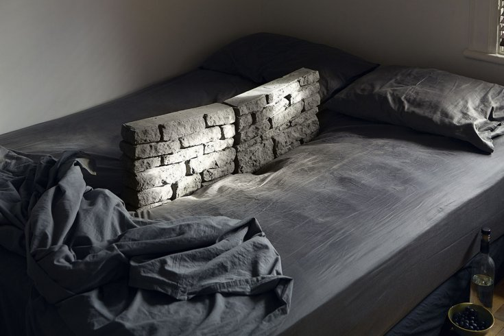 A bed with cement blocks on top of the mattress