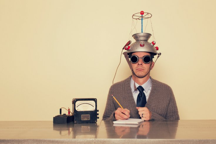 Photo of a man wearing a brain probe helmet made of a strainer