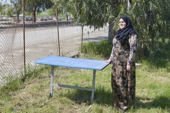 A woman wearing a hijab and a long dress standing with her hand on a blue table in a fenced-in area