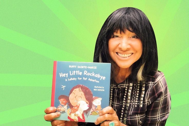A photograph of Buffy Sainte-Marie holding up her new picture book and smiling. The background is bright green with stripes radiating out from behind Buffy.