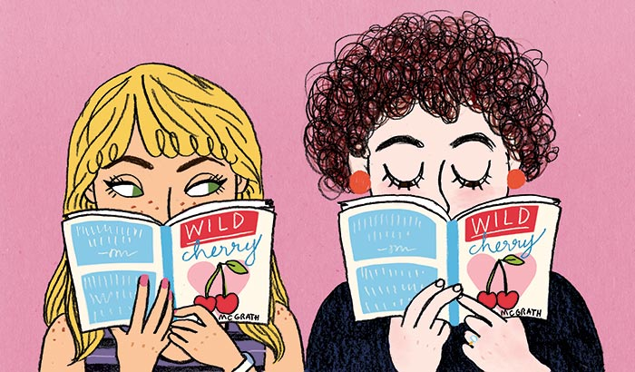 Two girls holding books in front of their faces