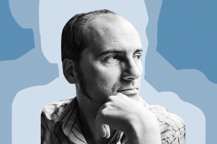 A photograph of the poet, a man with his chin in his hand and looking toward the right of the frame, against a periwinkle-blue background.
