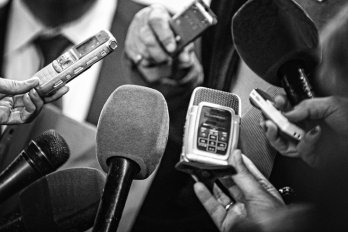 Journalists with tape recorders and microphones flocking around a suited person. The photo is in black and white.