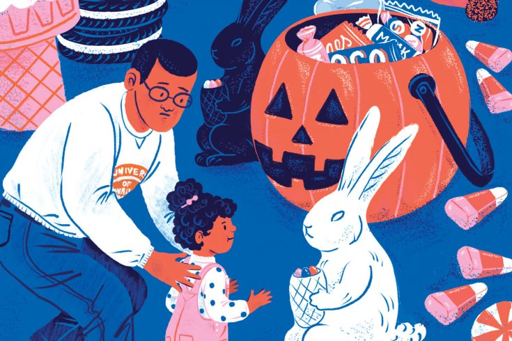 A man holds his young daughter back from approaching a rabbit that holds a bucket of Easter eggs. Behind the rabbit is a large pumpkin full of candy, with candy corn strewn around them.