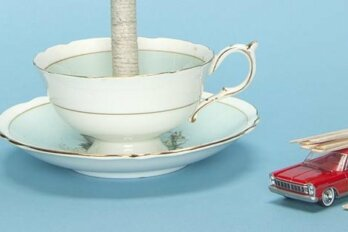 Illustration by Will Vincent; photograph by Adam Biehler. A close up shot of a tea cup on a saucer with a miniature red, toy car beside it.