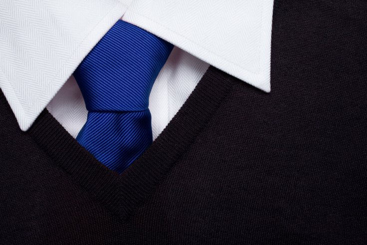 The knot of a blue tie stands out against a white collared shirt and black pullover sweater.