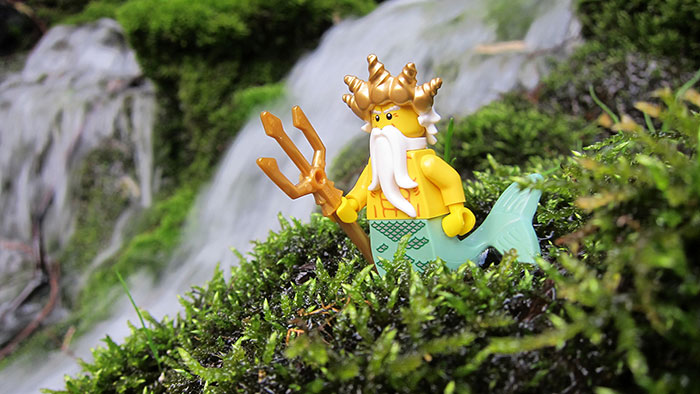 A Lego-mermaid standing on some grass