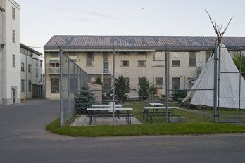 The outside of a jail, with an outdoor sitting area and tent