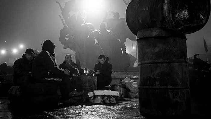 Black and white photo of men sitting outside